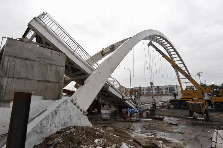 Men stand in front of a collapsed pedestrian bridge outside the Jawaharlal Nehru Stadium in New Delhi