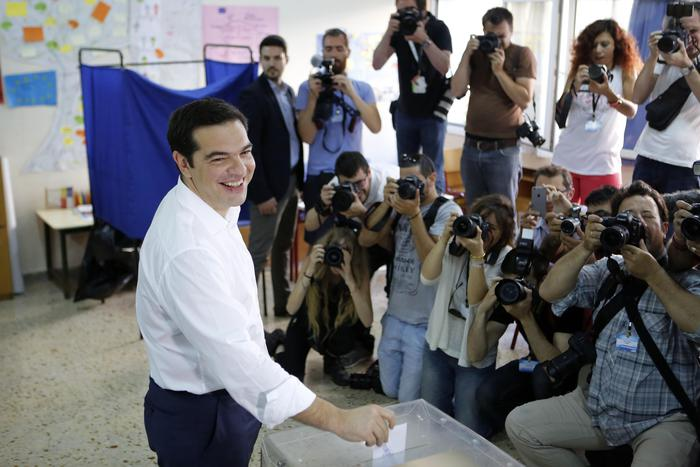 Greece's Prime Minister Alexis Tsipras casts his vote at a polling station in Athens, Sunday, July 5, 2015. Greeks began voting early Sunday in a closely-watched, closely-contested referendum, which the government pits as a choice over whether to defy the country's creditors and push for better repayment terms or essentially accept their terms, but which the opposition and many of the creditors paint as a choice between staying in the euro or leaving it. (ANSA/AP Photo/Petros Karadjias)