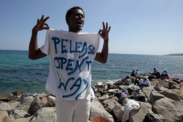 "A migrant shouts a slogan as he wears a Tee Shirt with the message, ""Open The Way"" as he stands on the seawall at the Saint Ludovic border crossing on the Mediterranean Sea between Vintimille, Italy and Menton, France, June 14, 2015. On Saturday, some 200 migrants, principally from Eritrea and Sudan who attempted to cross the border, were blocked by Italian police and French gendarmes.   REUTERS/Eric Gaillard   - RTX1GG1X"
