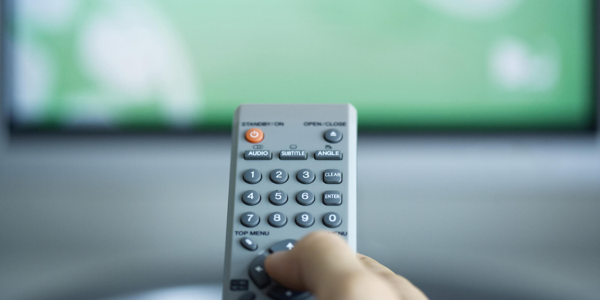 Person watching TV, using remote control to change channel, cropped