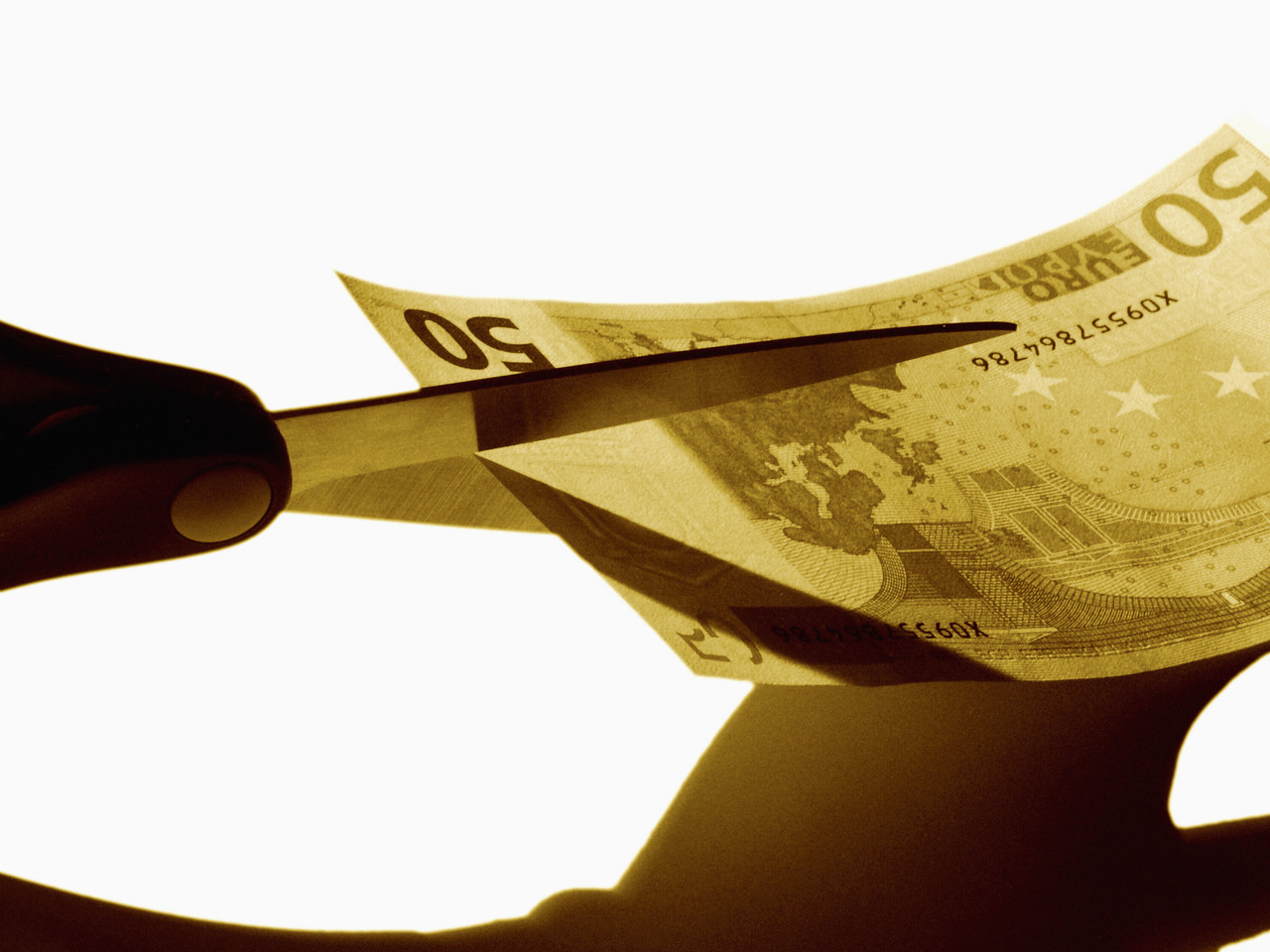 Scissors cutting money --- Image by © Royalty-Free/Corbis