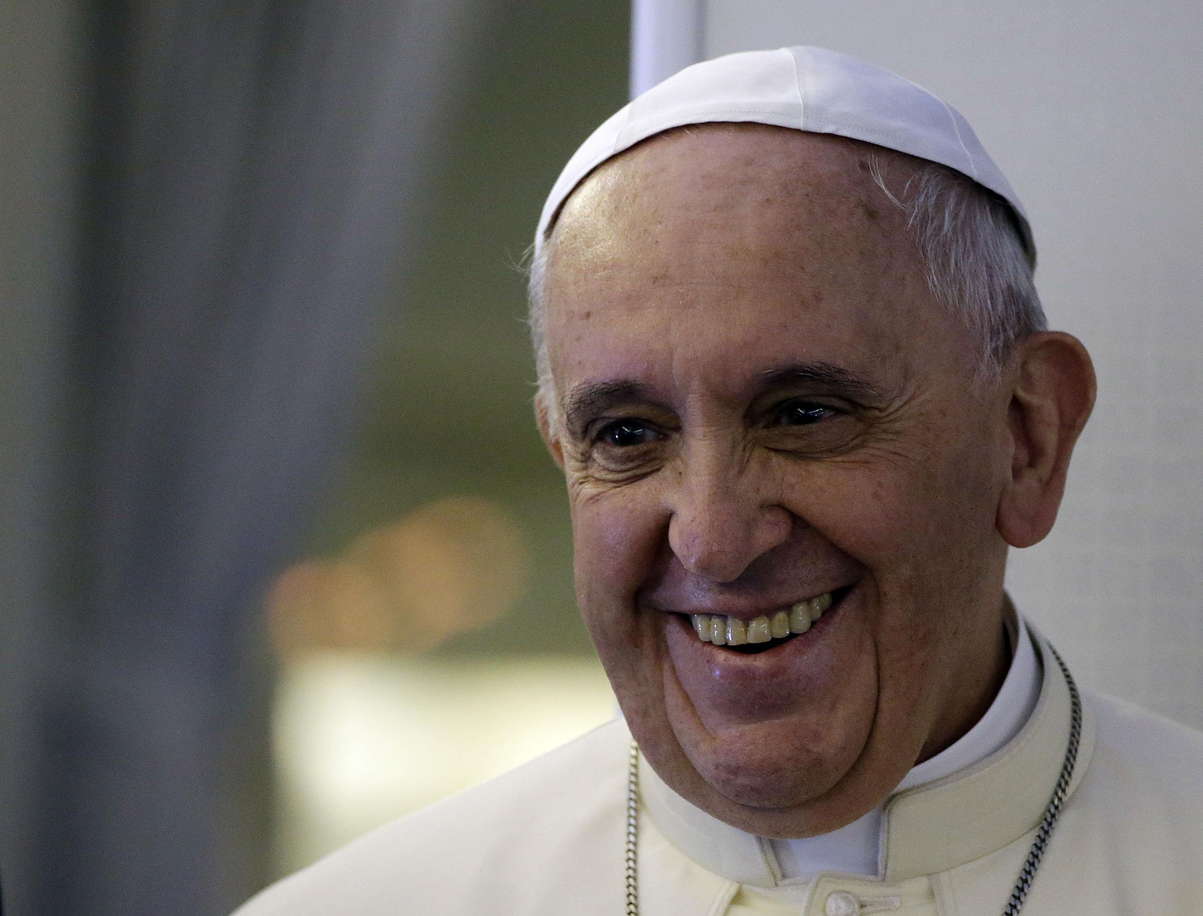 "Pope Francis smiles as he meets the media during an airborne press conference on his journey back to Rome from Seoul, South Korea, Monday, Aug. 18, 2014. Pope Francis wrapped up his first trip to Asia on Monday by challenging Koreans - from the North and the South -  to reject the ""mindset of suspicion and confrontation"" that cloud their relations and instead find new ways to forge peace on the war-divided peninsula. (AP Photo/Gregorio Borgia)"