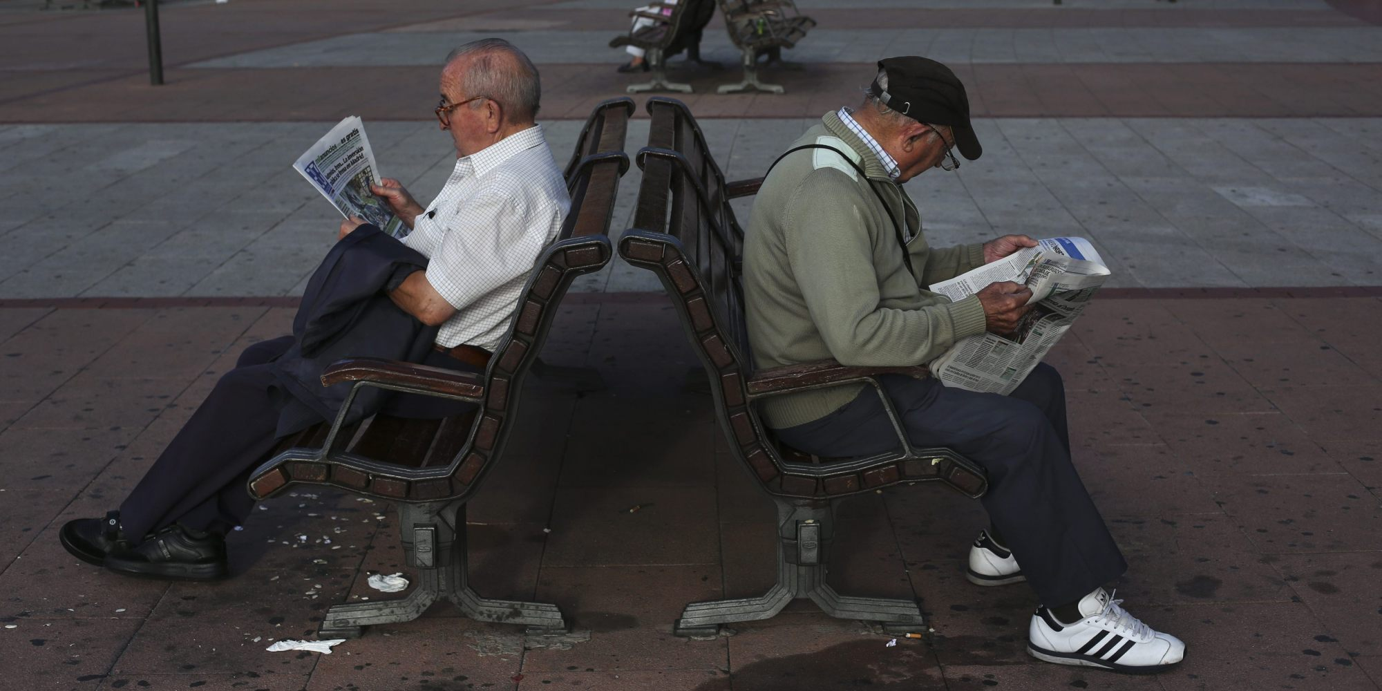 Pensioners read a free newspaper as they sit on public benches in Madrid October 2, 2013. Spain will use 11.6 billion euros ($15.70 billion) of the pension reserve fund in 2013 to pay pensions, Spain's Labour Minister Fatima Banez said on Tuesday. REUTERS/Susana Vera (SPAIN - Tags: BUSINESS EMPLOYMENT SOCIETY)