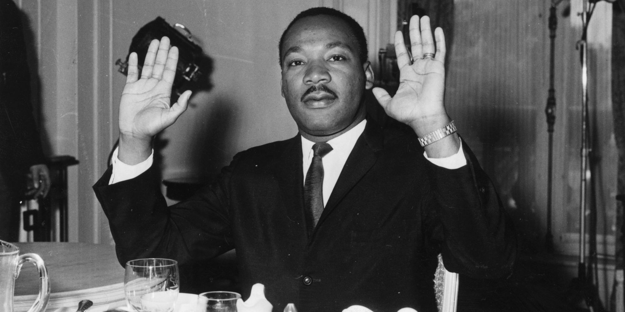 21st September 1963:  Black American civil rights leader and Baptist minister Dr Martin Luther King (1929  - 1968) raising his hands in a restaurant.  (Photo by William H. Alden/Evening Standard/Getty Images)