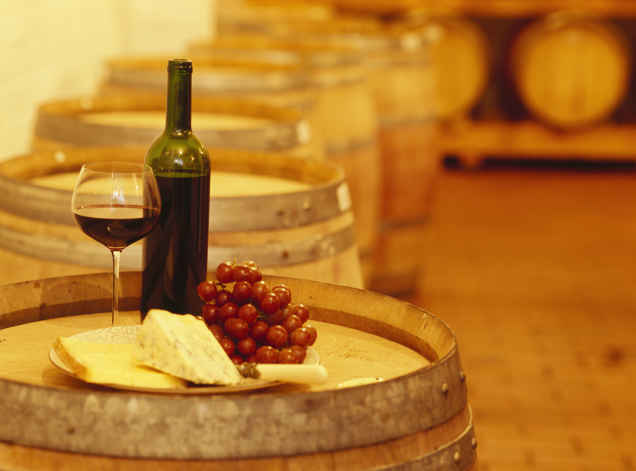 wine bottle with a wine glass and cheese on a barrel --- Image by © Royalty-Free/Corbis