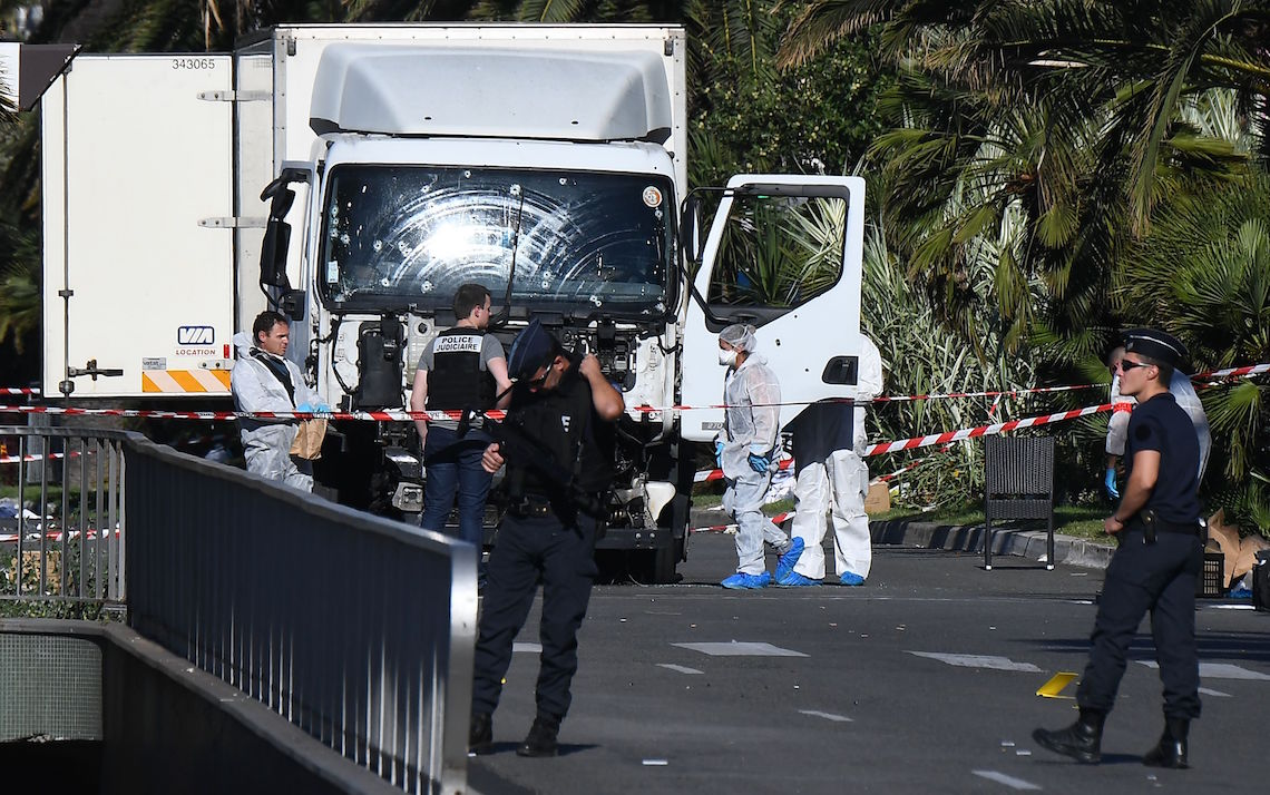 """Forensics officers and policemen look for evidences in a truck on the Promenade des Anglais seafront in the French Riviera town of Nice on July 15, 2016, after it drove into a crowd watching a fireworks display.An attack in Nice where a man rammed a truck into a crowd of people left 84 dead and another 18 in a """"critical condition"""", interior ministry spokesman Pierre-Henry Brandet said Friday. An unidentified gunman barrelled the truck two kilometres (1.3 miles) through a crowd that had been enjoying a fireworks display for France's national day before being shot dead by police. / AFP / ANNE-CHRISTINE POUJOULAT        (Photo credit should read ANNE-CHRISTINE POUJOULAT/AFP/Getty Images)"""