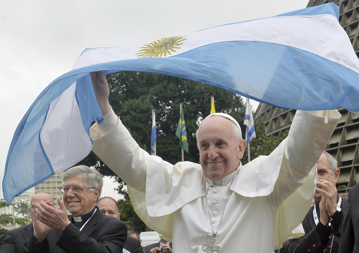"Pope Francis holds up an Argentine flag outside the Metropolitan Cathedral in Rio de Janeiro, Brazil, July 25, 2013. Francis added a last-minute tweak to his busy schedule, meeting with pilgrims from his native Argentina at Rio's cathedral Thursday afternoon. He told the youngsters to get out into the streets and spread their faith, saying that a church that doesn't go out and preach becomes a simple NGO, or nongovernmental organization. ""And the church cannot be an NGO!"" he said to applause.  (AP Photo/Luca Zennaro, Pool)"